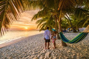 DMR0105AW Mano Juan, Saona Island, East National Park (Parque Nacional del Este), Dominican Republic, Caribbean Sea. Couple enjoying the sunset from the beach (MR).