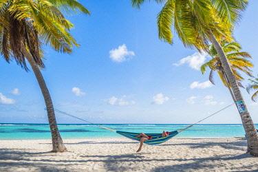 DMR0115AW Canto de la Playa, Saona Island, East National Park (Parque Nacional del Este), Dominican Republic, Caribbean Sea. Woman relaxing on a hammock on the beach (MR).