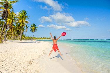 DMR0123AW Canto de la Playa, Saona Island, East National Park (Parque Nacional del Este), Dominican Republic, Caribbean Sea. Woman jumping happy on the beach (MR).