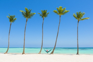 Juanillo Beach (playa Juanillo), Punta Cana, Dominican Republic. Woman relaxing on a hammock on a palm-fringed beach (MR).