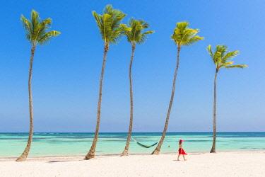 DMR0137AWRF Juanillo Beach (playa Juanillo), Punta Cana, Dominican Republic. Woman walking on a palm-fringed beach (MR).