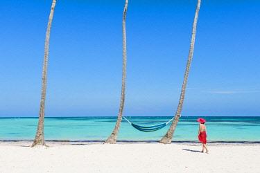 DMR0145AWRF Juanillo Beach (playa Juanillo), Punta Cana, Dominican Republic. Woman walking on a palm-fringed beach (MR).