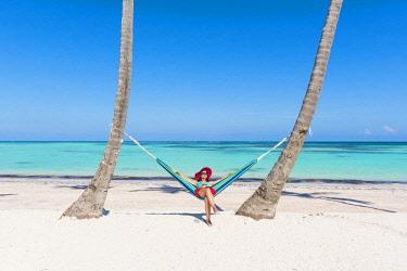 DMR0146AWRF Juanillo Beach (playa Juanillo), Punta Cana, Dominican Republic. Woman relaxing on a hammock on the beach (MR).