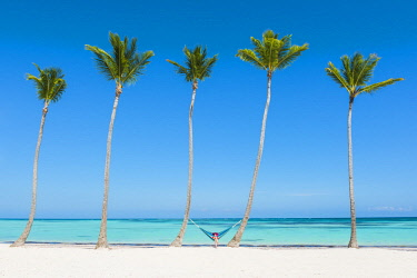 DMR0147AWRF Juanillo Beach (playa Juanillo), Punta Cana, Dominican Republic. Woman relaxing on a hammock on a palm-fringed beach (MR).