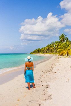 DMR0165AWRF Canto de la Playa, Saona Island, East National Park (Parque Nacional del Este), Dominican Republic, Caribbean Sea. Beautiful woman on a palm-fringed beach (MR).