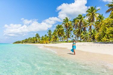 DMR0166AWRF Canto de la Playa, Saona Island, East National Park (Parque Nacional del Este), Dominican Republic, Caribbean Sea. Beautiful woman on a palm-fringed beach (MR).