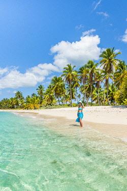 DMR0167AWRF Canto de la Playa, Saona Island, East National Park (Parque Nacional del Este), Dominican Republic, Caribbean Sea. Beautiful woman on a palm-fringed beach (MR).