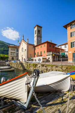 ITA10268AWRF Torno, lake Como, Como province, Lombardy, Italy. Morred boats and the town's church at the jetty,