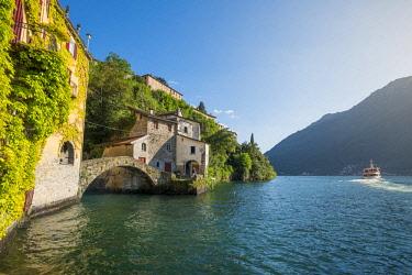 ITA10269AWRF Nesso, lake Como, Como province, Italy. The roman stone bridge and a tourist boat passing on the lake.