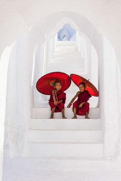 MYA2146AW Two Buddhist novice monks on the steps of the white pagoda of Hsinbyume (Myatheindan) paya temple, Mingun, Sagaing region, Myanmar