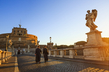 ITA10374AW Italy, Rome, two monks walking at Mausoleum of Hadrian (known as Castel Sant'Angelo)  at sunrise