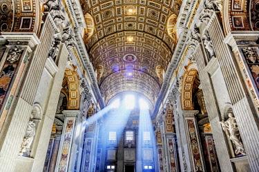 ITA10378AW Italy, Rome, St. Peter Basilica interior with sun lights penetrating through the windows at sunrise