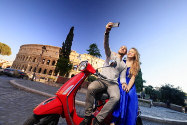 ITA10569AW Italy, Rome, a young couple on a red Vespa motorbike enjoying the sunset at Colosseum and Roman Forum