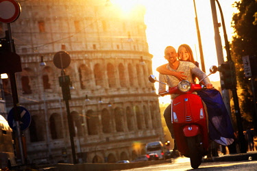 ITA10576AW Italy, Rome, a young couple on a red Vespa motorbike enjoying the sunset at Colosseum and Roman Forum