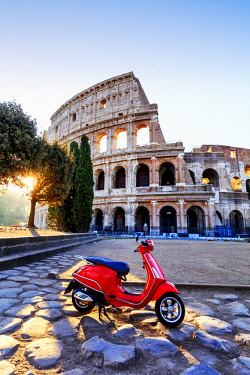 ITA10589AW Italy, Rome, a red Vespa motorbike in front of Colosseum at sunrise