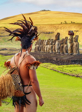 CHI10744AW Native Rapa Nui man in tradititional costume and Moais in Ahu Tongariki, Rapa Nui National Park, Easter Island, Chile. MR