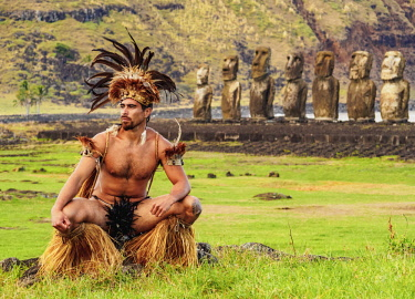 CHI10749AW Native Rapa Nui man in tradititional costume and Moais in Ahu Tongariki, Rapa Nui National Park, Easter Island, Chile. MR