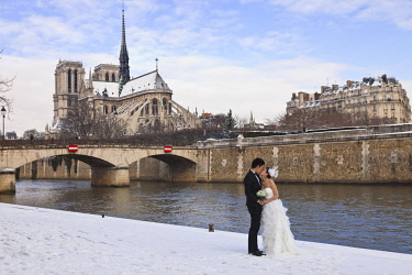 HMS1514587 France, Paris, wedding photo on the Saint Michel docks and Notre Dame Cathedral in the snow