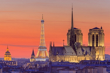HMS1905104 France, Paris, elevated view of the illuminated Eiffel Tower , the Notre Dame cathedral on Ile de la Cite, the Invalides dome and the Saint Germain des Pres church with Parisian rooftops at sunset