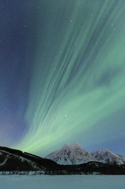 CLKFB59298 Aurora Borealis illuminates the landscape with views of the Lyngen Alps. Svensby, Ullsfjorden, Lyngen Alps, Troms, Norway, Lapland, Europe.
