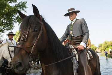 SPA7284AW Horse rider on the Quema river. El Rocio pilgrimage, Andalusia. Spain