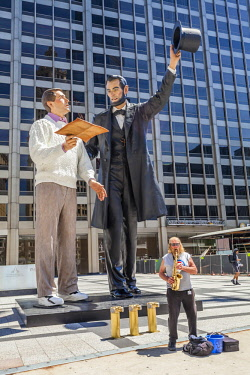 USA12754AW A large version of American realist artist, Seward Johnson's 'Return Visit' sculpture. It is installed in Pioneer Court.  Abraham Lincoln handing a copy of the Gettysburg Address to a modern-day man w...