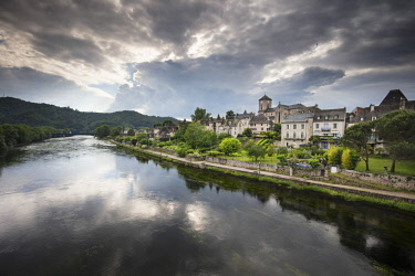 FRA9700AW France, Correze, Argentat, The old town and riverbank reflected in the Dordogne river with a moody sky