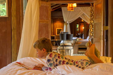 TZ02187 Child reading on bed, Lake Manyara Tree Lodge, Tanzania