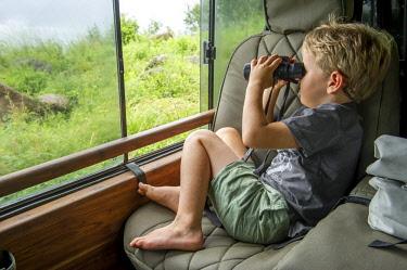 TZ02188 Child looking through binoculars, Lake Manyara, Tanzania