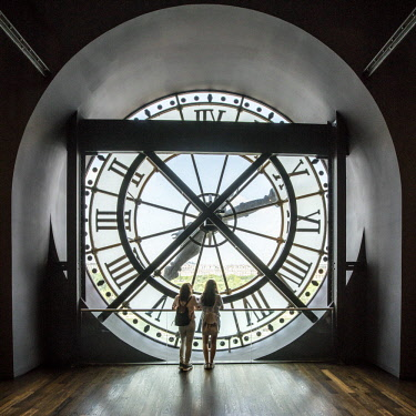 FRA9859AW Two girls looking through a giant clock in Musee d'Orsay, Paris, France