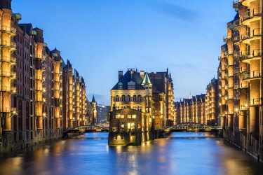 GER9952AW Germany, Hamburg, Speicherstadt. Historic Wasserschloss at dusk, view from the Poggenmuhlenbrucke.