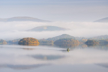 ENG14612AW Single sculler rowing across a misty Derwent Water at dawn, Lake District, Cumbria, England. Autumn (October) 2016.