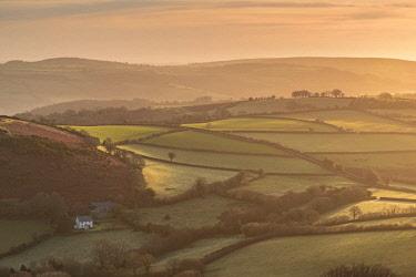 ENG14615AW Farmhouse in idyllic rolling countryside at dawn, Dartmoor National Park, Devon, England. Winter (March) 2017.