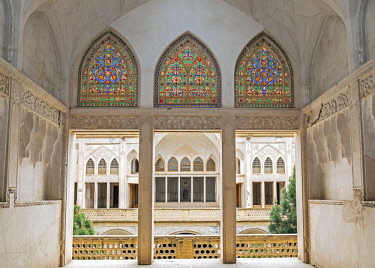 IRA1227 Iran, Kashan. An upstairs view of Abbasian Historic House with stained glass windows. This beautiful house was built in 1823 and took 20 years to complete.  It was said to have been the property of a...