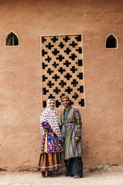 IRA1237 Iran, Abyaneh. A young couple beside an old red mud-plastered building in Abyaneh village. The village is one of the oldest and most traditional in Iran, attracting many tourists.