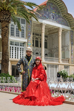IRA1326 Iran, Shiraz. A newly-wed Iranian couple in traditional costume pose in front of the Qajari-era palace, Kakh-e Eram, in Eram garden which is a UNESCO World Heritage Site.