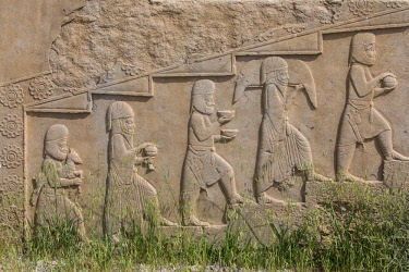 IRA1347 Iran, Persepolis. A bas-relief of men bearing gifts for the king decorate stairway of the �Tachara'. Persepolis was the ceremonial capital of the Achaemenid Empire dating back to 515 BC.