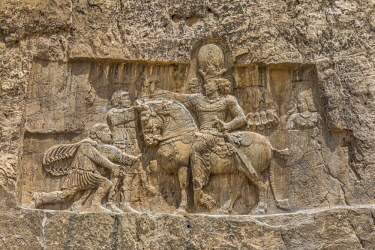 IRA1360 Iran, Naqsh'e Rostam. The most famous of the Sassanid Bas-reliefs depicts the triumph of Shapur I over two Roman emperors, Valerian Caesar and Philip the Arab. Behind the king stands Kirtir, a powerfu...