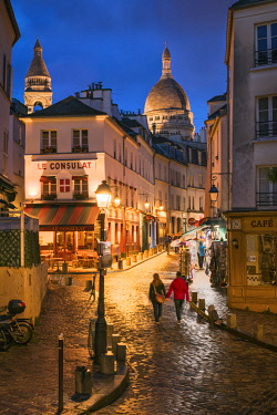 FRA10050AW Tourist couple walking along the streets of Montmartre at night with illuminated Sacre Coeur Basilica in the background, Paris, France