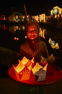 AS38DWA0037 Elderly woman selling floating candle lanterns, Hoi An (UNESCO World Heritage Site), Vietnam