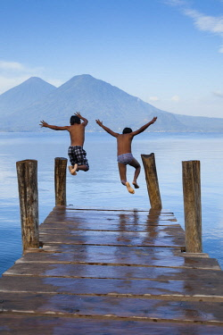 SA10BTH0000 Guatemala, Lake Atitlan. Young boys having fun while swimming in the lake.