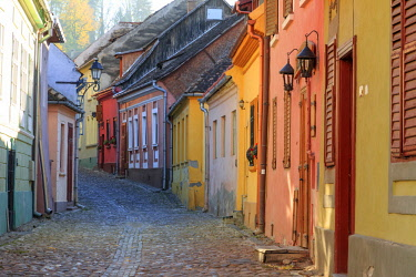 EU24EWI0200 Transylvania, Romania, Mures County, Sighisoara, cobblestone residential street of colorful houses in village. UNESCO World Heritage Site.