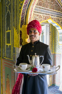IN05661 India, Rajasthan, Jaipur, Samode Palace, Waiter carrying Tea Tray in ornate passageway (MR, PR)