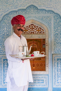 IN05663 India, Rajasthan, Jaipur, Samode Palace, Waiter carrying Tea Tray in ornate passageway (MR, PR)