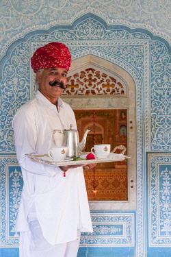 IN05663 India, Rajasthan, Jaipur, Samode Palace, Waiter carrying Tea Tray in ornate passageway (MR, PR)