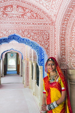 IN05667 India, Rajasthan, Jaipur, Samode Palace, lady wearing a colourful Sari in ornate passageway (MR, PR)