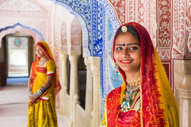 IN05668 India, Rajasthan, Jaipur, Samode Palace, ladies wearing a colourful Sari in ornate passageway  (MR, PR)