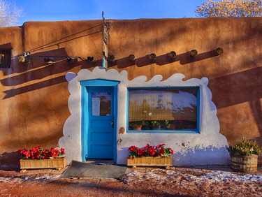 US32TEG0051 USA, New Mexico, Sant Fe, Adobe structure with protruding vigas and Blue Door