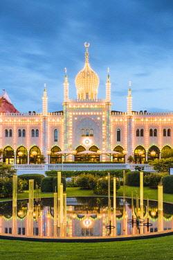 DEN0341AW Tivoli gardens, Copenhagen, Hovedstaden, Denmark. The Nimb Hotel illuminated at dusk in summer.