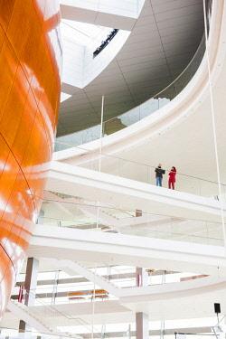 DEN0372AW National Opera House, Copenhagen, Hovedstaden, Denmark. Two people walking on a balcony in the foyer.
